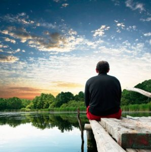Image of man sitting on dock enjoying lake sunrise