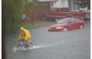 image of person riding bike through flooded Yorkton street