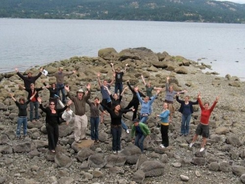 image of a group of people standing with arms extended on a rocky shore