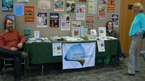 image of a table with information pamphlets and 2 people sitting at either end