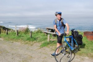 image of young man beside bike along water's edge